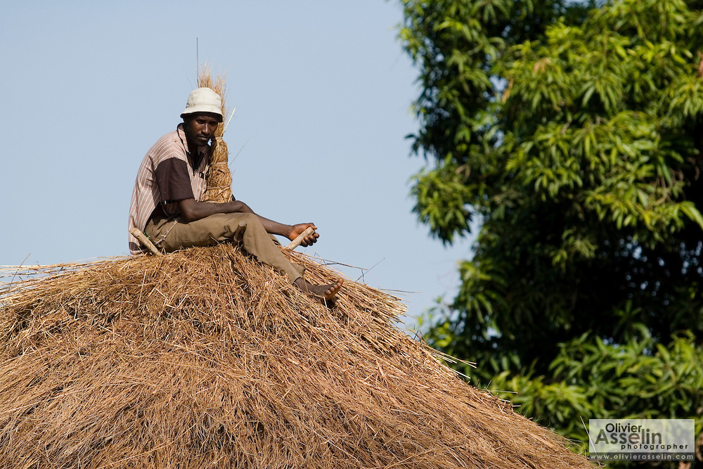Man working on roof in the village of Darou Hidjeratou, Senegal, on Tuesday June 19, 2007.