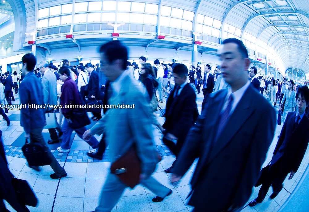 Many commuters walking to work in a busy railway station in Tokyo Fish eye and blue tint