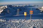 A warning sign on alpine mountain top for skiers, telling them of a closed piste and of no marked and controled trail.