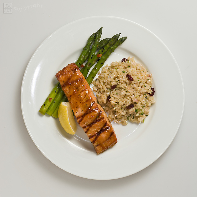 grilled salmon filet with asparagus and rice on white plate with lemon