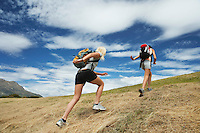 Two women running up hill back view