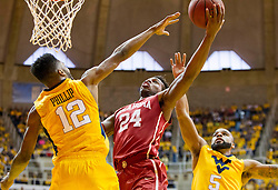 Feb 20, 2016; Morgantown, WV, USA; Oklahoma Sooners guard Buddy Hield (24) shoots over West Virginia Mountaineers guard Tarik Phillip (12) during the first half at the WVU Coliseum. Mandatory Credit: Ben Queen-USA TODAY Sports