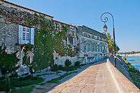 Historic buildings as part of the town wall along the Rhone river in Arles, France.