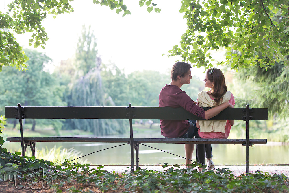 Romantic young couple sitting on park bench by lake