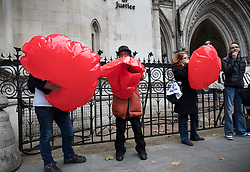 © Licensed to London News Pictures. 29/11/2017. London, UK. Supporters of Lauri Love inflate heart shaped balloons outside the High Court. Mr Love is appealing extradition to the US over alleged cyber-hacking. Photo credit: Peter Macdiarmid/LNP