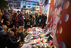 © Licensed to London News Pictures. 11/01/2016. People gather round a mound of flowers and cards placed in front of a mural of David Bowie. The Death of David Bowie has been announced. Bowie was born in Brixton.  Photo credit: Peter Macdiarmid/LNP
