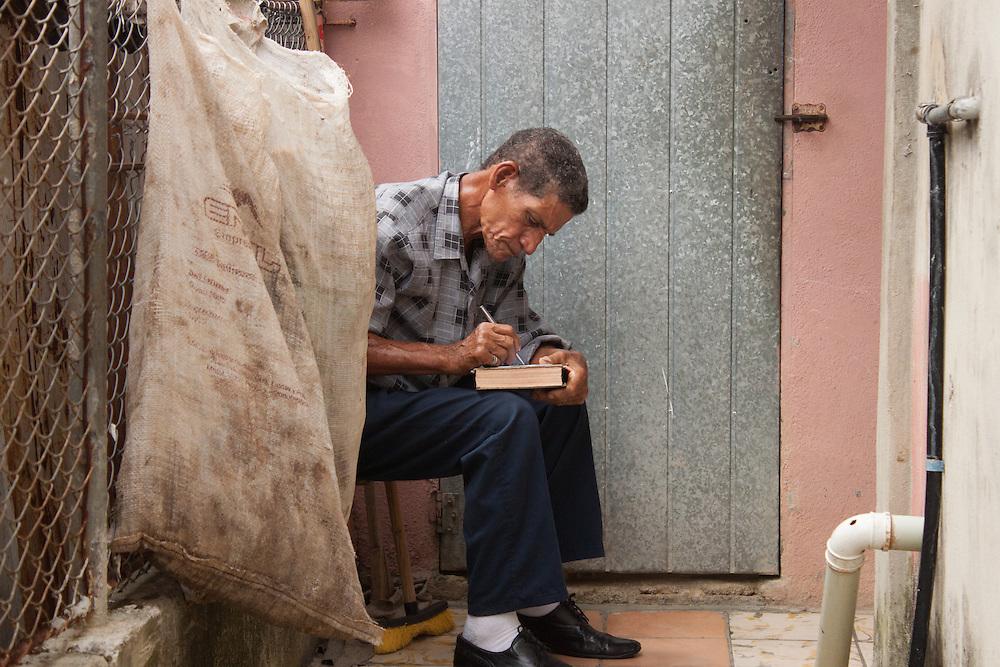 man writing and taking sermon notes