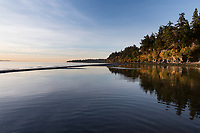 At low tide a sandbar appears in Cordova Bay, in Victoria, BC and the sunrise turns the sand gold and red.