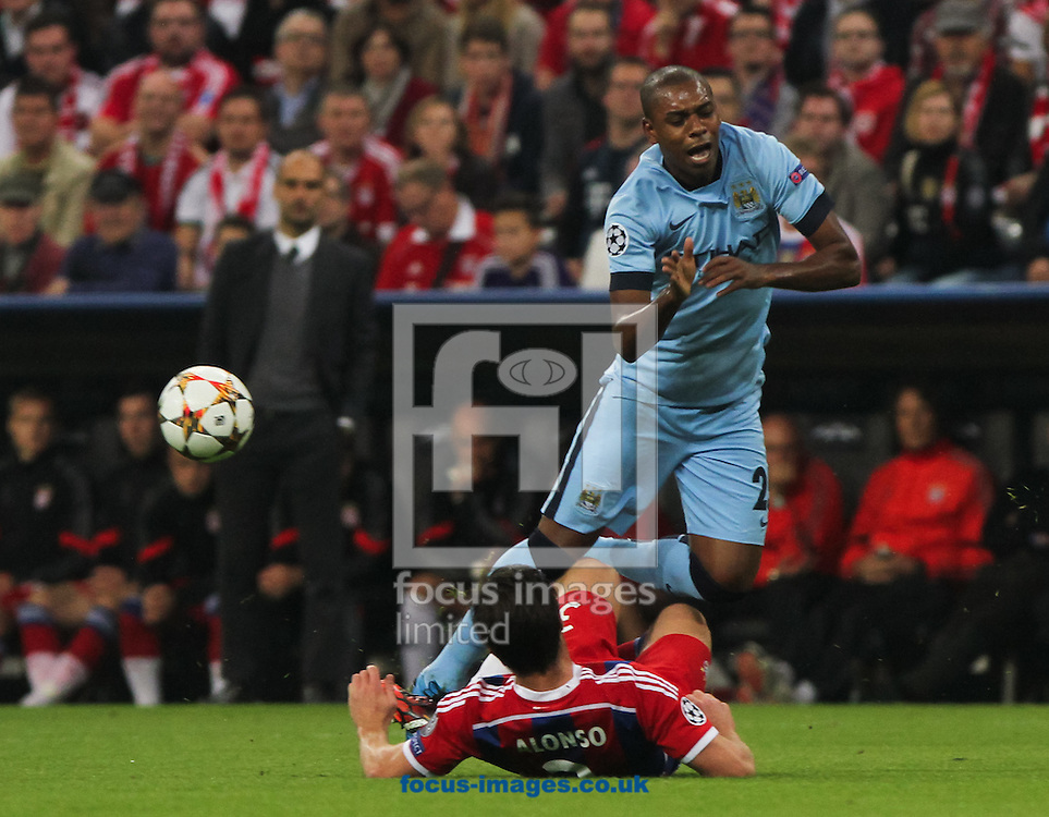 Xabi Alonso (centre) of Bayern Munich fouls Fernandinho (right) of Manchester City during the UEFA Champions League match at Allianz Arena, Munich<br /> Picture by Tom Smith/Focus Images Ltd 07545141164<br /> 17/09/2014