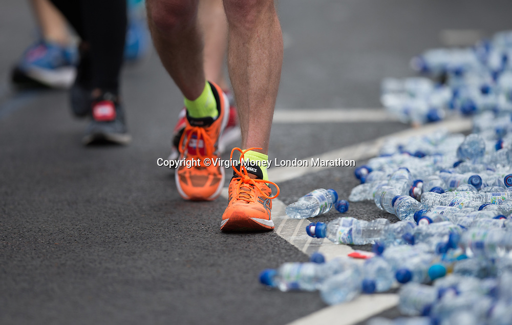 A runner passes discarded Buxton water bottles. The Virgin Money London Marathon, Sunday 24th April 2016.<br /> <br /> Photo: Joe Toth for Virgin Money London Marathon<br /> <br /> For more information please contact media@londonmarathonevents.co.uk