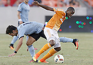 Jun 29, 2016; Houston, TX, USA; Sporting Kansas City midfielder Benny Feilhaber (10) and Houston Dynamo midfielder Oscar Garcia (27) fight for possession in the second half at BBVA Compass Stadium. Dynamo won 3 to 1. Mandatory Credit: Thomas B. Shea-USA TODAY Sports