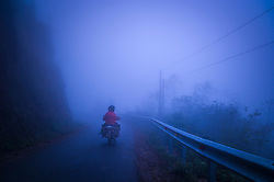 Single motorbike drives along a misty road between Dong Van and Lung Cu in Ha Giang Province, Vietnam, Southeast Asia