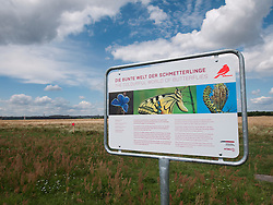Sign information about butterflies at new city public Tempelhofer Park on site of famous former Tempelhof Airport in Berlin Germany