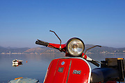 A bright red moped parked up with sea and mountains behind it.
