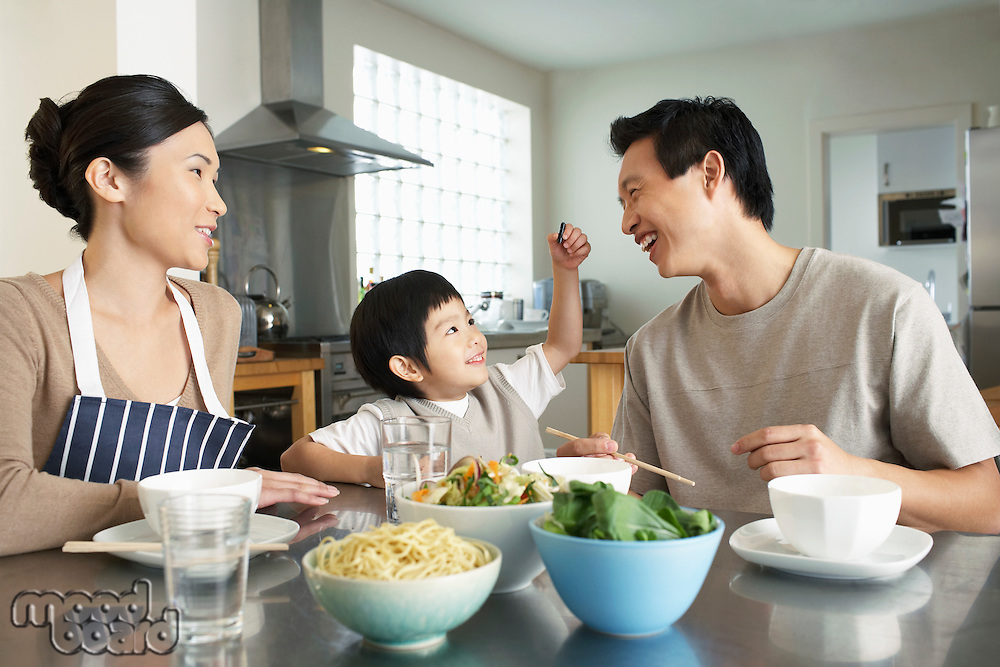 Young Family sitting at kitchen table interacting before meal