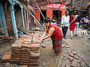 30 JULY 2015 - KATHMANDU, NEPAL:    A woman collects clay bricks for recycling and reuse around her home in Kathmandu that was destroyed in the Nepal Earthquake. The Nepal Earthquake on April 25, 2015, (also known as the Gorkha earthquake) killed more than 9,000 people and injured more than 23,000. It had a magnitude of 7.8. The epicenter was east of the district of Lamjung, and its hypocenter was at a depth of approximately 15km (9.3mi). It was the worst natural disaster to strike Nepal since the 1934 Nepal–Bihar earthquake. The earthquake triggered an avalanche on Mount Everest, killing at least 19. The earthquake also set off an avalanche in the Langtang valley, where 250 people were reported missing. Hundreds of thousands of people were made homeless with entire villages flattened across many districts of the country. Centuries-old buildings were destroyed at UNESCO World Heritage sites in the Kathmandu Valley, including some at the Kathmandu Durbar Square, the Patan Durbar Squar, the Bhaktapur Durbar Square, the Changu Narayan Temple and the Swayambhunath Stupa. Geophysicists and other experts had warned for decades that Nepal was vulnerable to a deadly earthquake, particularly because of its geology, urbanization, and architecture.     PHOTO BY JACK KURTZ