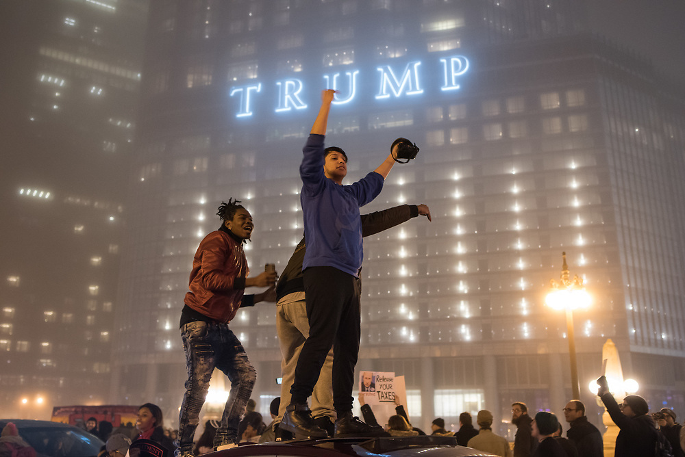 Anti-Trump protesters gather atop a car in front of Trump Tower in Chicago during a mass demonstration on Inauguration Day on January 20, 2017.