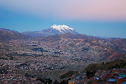 Aerial view of the city of La Paz and Mount Illimani (6402m) at dusk with pink light,  La Paz,  Bolivia, South America