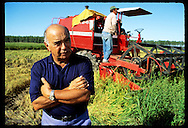 Erico Ribeiro, world's largest rice grower, stands near rice combine on harvest morn at farm. Brazil