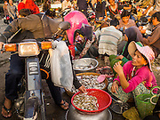 25 FEBRUARY 2015 - PHNOM PENH, CAMBODIA:  A man on a motorcycle buys fish in a market in Phnom Penh.   PHOTO BY JACK KURTZ