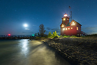 The moon and stars shine brightly over Holland Lighthouse