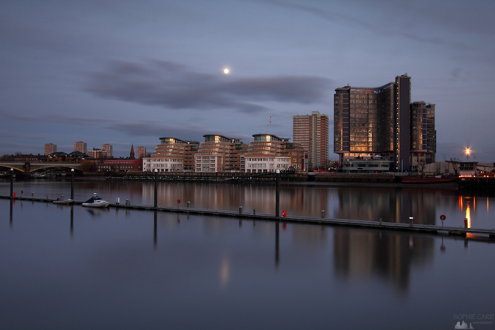 Long exposure shot of the River Thames in London just as the sun sets and the moon rises, This is a newish block at Battersea on the south of the river; on the right is a helicopter port.