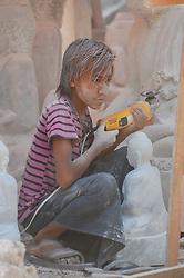 A boy works carving marble statues in Mandalay, Burma (Myanmar)