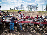 """20 APRIL 2020 - BOUTON, IOWA: A farmer and his son work on his tiller in a field near Bouton. Iowa farmers are prepping their fields for the 2020 season. The relatively mild winter and dry spring has allowed farmers to get into their fields 1 - 2 weeks earlier than last year. Farmers and agricultural workers are considered """"essential"""" workers in Iowa and not subjected to the coronavirus restrictions nonessential workers are. Farmers usually work by themselves, and social distancing guidelines have not impacted them as much as it has workers in Iowa's cities.   PHOTO BY JACK KURTZ"""