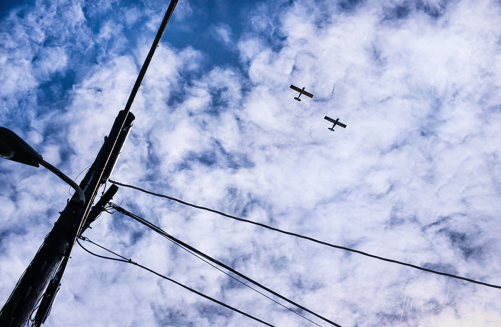 Two airplanes fly overhead, in a windswept cloudy blue sky, framed by powerlines.