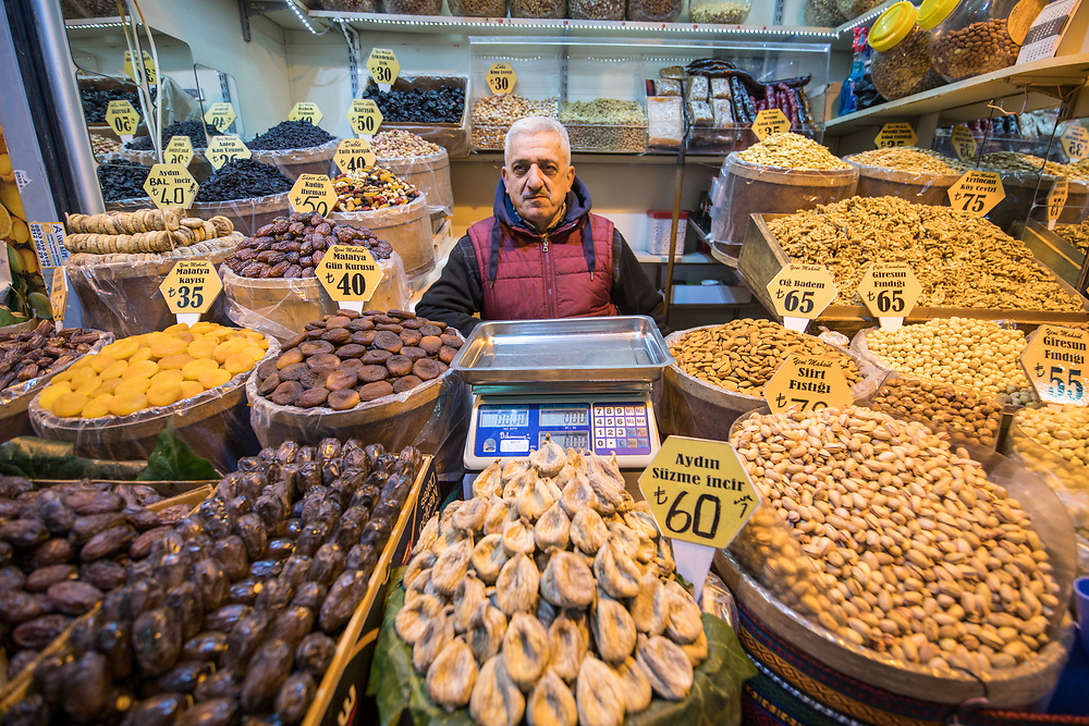 Adult male shop merchant stands behind counter that has baskets full of dried fruits and nuts for sale at Istanbul Spice bazaar in Turkey