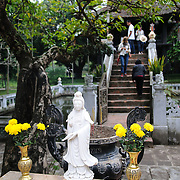 Tourists walk the short flight of stairs to the historic, small One Pillar Pagoda sitting in the center of a small pond near the Ho Chi Minh Museum in the Ba Dinh district of Hanoi. It is one of the most iconic temples in Vietnam and dates back to the 11th century.