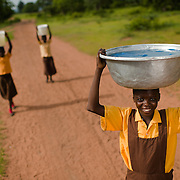 Tommy on her way to school with a basin of water in the Upper West Region of Ghana on 27 May 2014. The government school in her village has no water, and so students—only girls, not boys—must carry water from the river about a kilometre away to school every day.