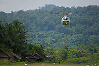 Helicopter arrives at Kwerba Village to airlift the expedition team into the Foja Mountains.
