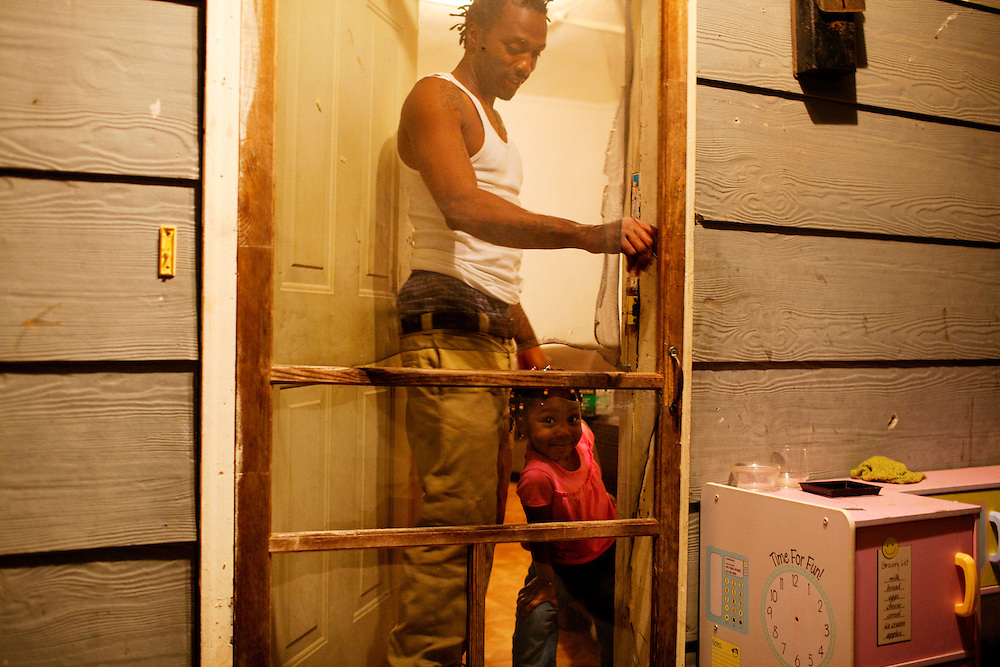 "Roger ""Winky"" Williams stands in the doorway of his home with his daughter Cameariyana, 4, in the Baptist Town neighborhood of Greenwood, Mississippi on February 16, 2011."