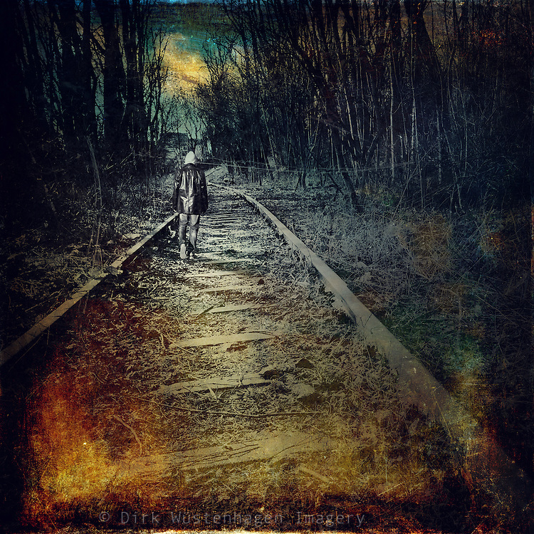 Man walking alone on an abandoned railroad track - texturized and manipulated photograph