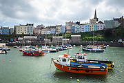 Pleasure boats - powerboats and yachts in harbour at high tide - seaside housing and town behind, Tenby, Wales, UK