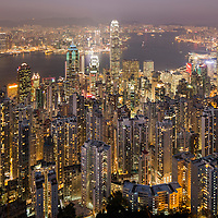 China, Hong Kong, View of glowing skyscrapers in city skyline from viewpoint atop Victoria Peak at twilight on winter evening