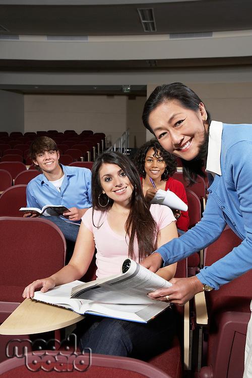 Teacher explaining something to female student