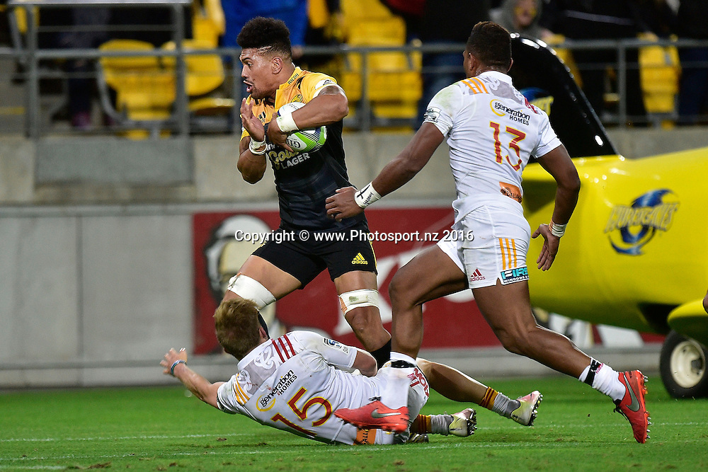 Hurricanes' Ardie Savea (L) runs with the ball with Chiefs' Damian McKenzie (Bottom) and Seta Tamanivalu (R during the Hurricanes vs Chiefs Super Rugby match at the Westpac Stadium in Wellington on Saturday the 23rd of April 2016. Copyright Photo by Marty Melville / www.Photosport.nz