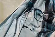 A detail of a crumpled advertising poster in a display window featuring a smiling model wearing glasses, on 2nd October 2019, in Sutton, London, England