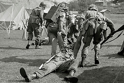 """Members of the US 82nd Airborne/505th RCT living History Group take part in the first days battle re-enactment at Fort Paull. Reenactors pulling a """"casualty"""" off the field as the Americans are pushed back <br /> <br />   03 May 2015<br />   Image © Paul David Drabble <br />   www.pauldaviddrabble.co.uk"""
