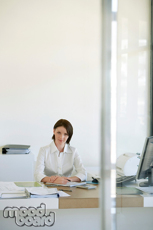 Businesswoman sitting at desk in office front view.