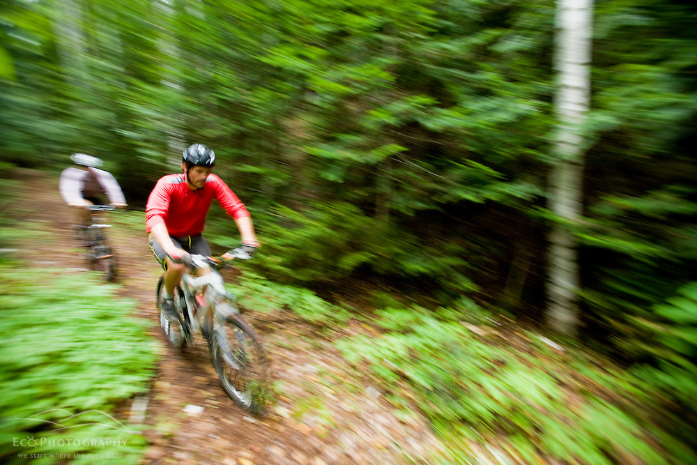 A couple mountain biking at Moose Brook State Park in Gorham, new Hampshire.