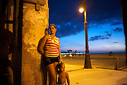 A Cuban woman who has lived along the seafront Malecon for years, waits to be relocated to new housing to make way for a 5-star hotel in Central Havana. Cubans wonder whether the coming tourism wave and political opening with the U.S. will alter their lives for the better.