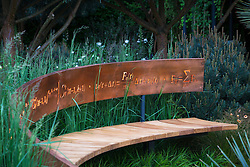 Curved bench seat decorated with mathematical symbols cut into band of copper which are illuminated at night. The Winton Beauty of Mathematics Garden, Chelsea Flower Show 2016