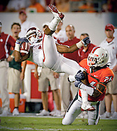 Oklahoma's Mossis Madu is taken down by Miami's Ray Ray Armstrong as the University of Miami hosts Oklahoma University at Land Shark Stadium at Miami Gardens, Florida on Saturday, October 2, 2009.