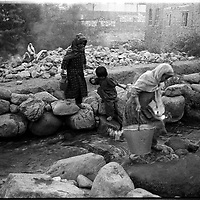 Refugee children collect water from a stream feeding the Panshir. All women except children have to wear the burqa.  Women have to be covered at all times, even in areas controlled by the more lenient Northern Alliance, but in Taliban areas, they tempt death to show the slightest deviance from repressive tribal interpretation of Islam. (Greg Marinovich)