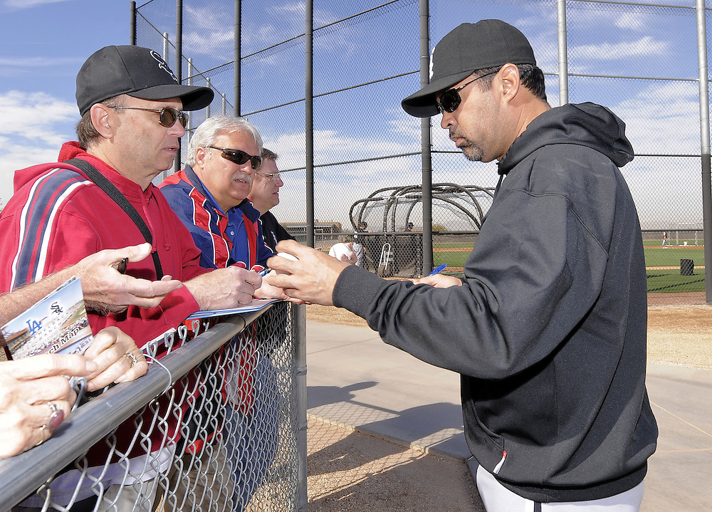 GLENDALE, AZ - FEBRUARY 25:  Manager Ozzie Guillen #13 of the Chicago White Sox signs autographs during a spring training workout on February 25, 2011 at Camelback Ranch in Glendale, Arizona. (Photo by Ron Vesely)
