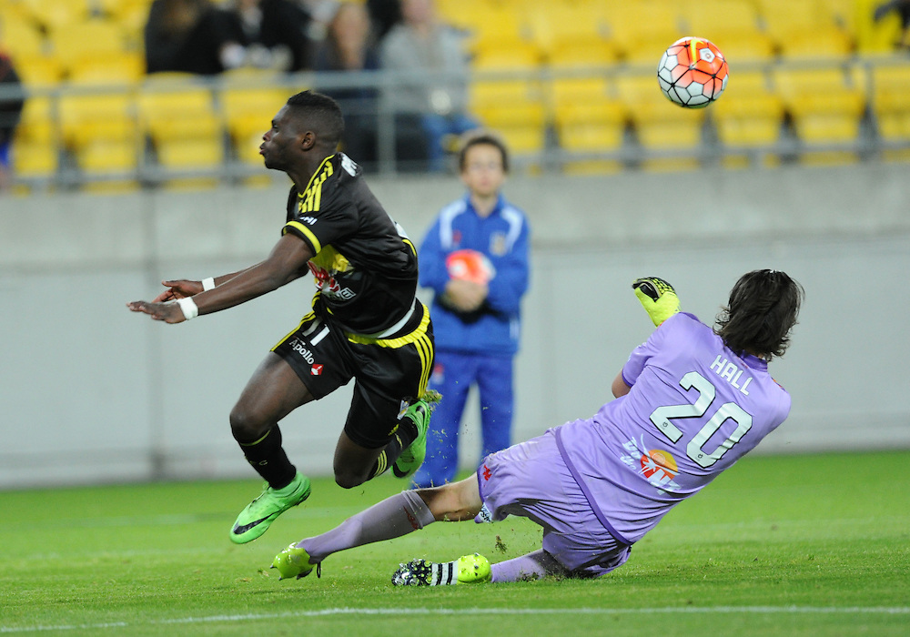Phoenix's Kwabena Appiah-Kubi, left, clashes with Adelaide United's goalie John Hall in the A-League football match at Westpac Stadium, Wellington, New Zealand, Friday, November 13, 2015. Credit:SNPA / Ross Setford