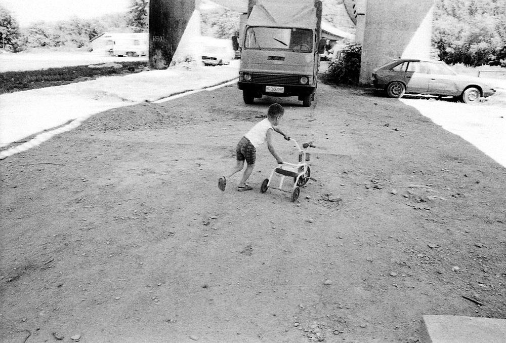 An improvised playground...During the summer1999, over 245,000 Serbs and Roms fled to Serbia and Montenegro from or within Kosovo in fear of reprisals from the majority Albanian population, after NATO air strikes had forced the withdrawal of Yugoslav. In 2003, less than 2% of them had returned and a large number of these internally displaced persons (IDPs) were still living in camps in very difficult conditions..In addition, around 5,000 IDPs, mainly of Roma ethnicity, are living in unrecognized collective centres, makeshift huts, corrugated metal containers and other substandard shelters. .This work was meant to look at how the life of children and young adults is affected by the fact that they are IDPs. I asked myself more specifically what would be different for these children/young adults from the 'normal' people of their age as far as education, health, social life, family, 'love' life and leisure are concerned. ..Terrain de jeux improviisé...Pendant l'été 1999, plus de 245 000 serbes et roms ont fuit le Kosovo pour chercher refuge en Serbie ou au Montenegro, par peur de représailles de la part de la majorité de la population albanaise après que les forces de l'OTAN aient forcé l'armée yougoslave à se retirer. En 2003, moins de 2% d'entre eux étaient rentrés chez eux et le plus grand nombre de ces 'déplacés' (IDPs) vivaient encore dans des centres d'accueil dans des conditions très difficiles..Environ 5 000 IDPs, la plupart romas, vivent dans des centres non reconnus faits de containers ou d'abris de fortune. .Ce travail s'est focalisé sur les jeunes IDPs, sur les conséquences de leur état de 'déplacés' sur leur vie et plus particulièrement dans les sphères concernant l'éducation, la santé,  la vie sociale, la vie de famille, la vie amoureuse et les loisirs..